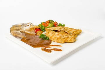 Grilled chicken breast with vegetable, baked potatoes, and a glass of black pepper gravy on white background