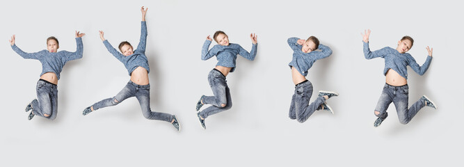 Happy excited boy the teenager jumps on a gray background.