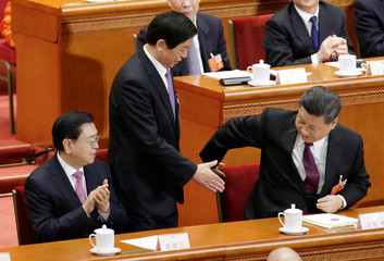 Newly elected Chairman of the Standing Committee of the NPC Li Zhanshu stretches to shake hands with Chinese President Xi Jinping next to former Chairman of the Standing Committee of the NPC Zhang Dejiang at the fifth plenary session of the NPC in Beijing