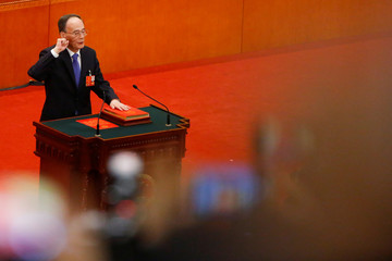 Newly elected Chinese Vice President Wang Qishan pledges an oath to the constitution during the National People's Congress at the Great Hall of the People in Beijing