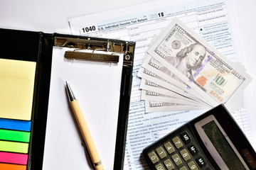 Tax form with notepad, pen and calculator on table.