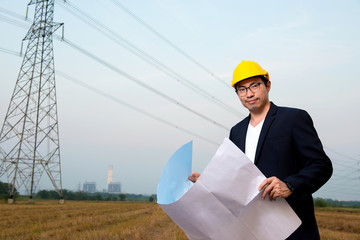 An engineer wear yellow hard hat and suite hold blueprint in hand standing on field looking at camera