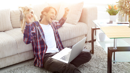 happy guy rejoicing and raising his hands sitting near the sofa