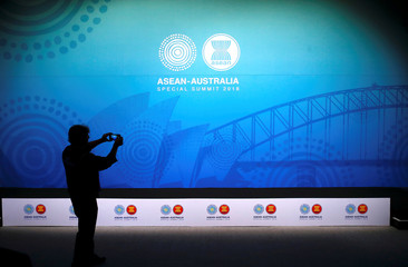 A cameraman takes a photograph using an iPhone of the stage for the Leaders Welcome and Family Photo during the one-off ASEAN summit in Sydney