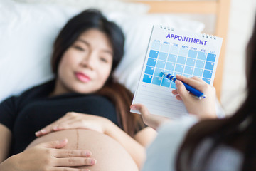 Selective focus Female Obstetrician doctor looking  a calendar and appointment pregnant woman patient for antenatal care or expected date of conifinement  /set Cesarean section date.