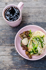 Thai style dry beef noodle on wooden table