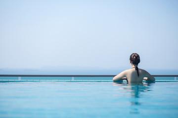 Woman in swim suit in swimming pool.
