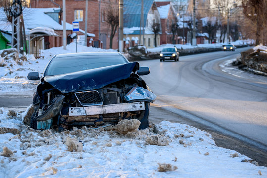 Car crash accident on street, damaged automobile after collision in city. Winter road, snowdrifts.