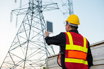 Electrical engineer working. Electrician holding tablet at high voltage power pylon against blue sky