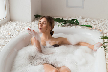 The place that leaves you feeling great! Attractive enjoying young girl blowing at the soap foam in the bath and having a great leisure time, while relaxing.