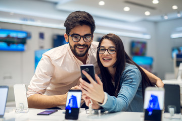 Close up focus view of a stylish charming embracing young student love couple taking a selfie with new mobile in a tech store.