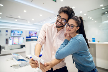 Portrait view of young cute love couple standing hugged in front of the desk with tablets and testing selfie operation in the tech store.
