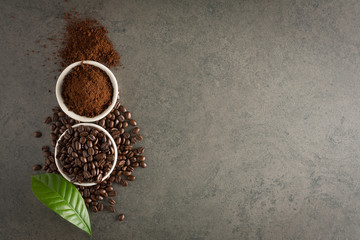 Coffee beans and ground powder with leaf on stone background. Top view with copy space