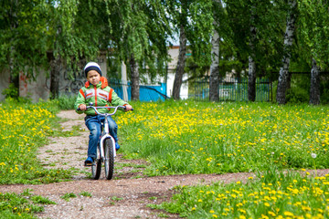 boy six years in a green jacket rides a bike in the park in the spring