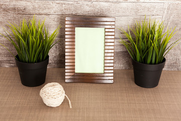 Close up of decorative photo frame next to two pots of grass and over vintage wooden background