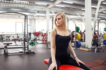 Young slender woman in gym posing against a lot of fitness equipment on background. She wears black T-shirt, pants and sneakers