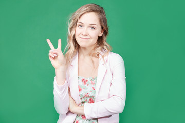 Fashionable female model with wavy hair, wears trendy colorful dress, round lips, gestures against green background, feels like star. Beautiful blonde woman shows peace sign. Body language concept.