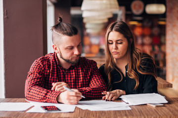 young entrepreneurs made a deal in a cafe, signing documents
