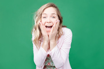 Amazed Caucasian female keeps mouth opened, hands on cheeks, being shocked to get wonderful surprise, stares at camera, isolated over green wall background. Pretty woman expresses great pleasure.