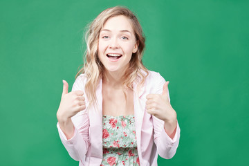 Portrait of young Caucasian female employee or customer with ultra white wide smile, looking at  camera with happy expression, showing thumbs-up with both hands, achieving career goals. Body language