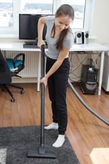 Apartment cleaning.A young European girl with long hair vacuuming a room