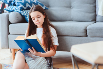 smart kid girl reading interesting book  at home, sitting with couch on background. Learning and education concept