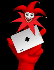 Human hand with a red smiled Joker head on the finger holding ace of Spades playing card isolated on the black background
