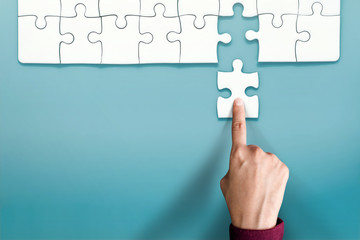 Complete Concept. Hand Replace a Final Jigsaw Puzzle Piece into a Last Blank. Symbolic of Teamwork and Business Success