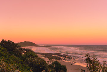 The Pinky sunset in summer time on the beach in Ballina with ocean view and hilly landscape, Byron bay, Australia