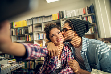 Concept of education, library, students and love. Satisfied productive young studying couple sitting in the library and learning together while taking a selfie for a break.