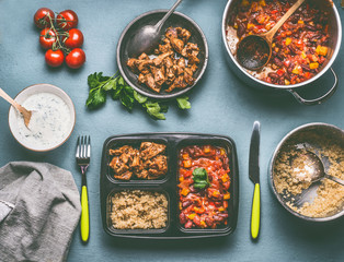 Healthy balanced lunch box preparation with quinoa, tomatoes beans sauce and chicken meat on kitchen table background with food pots and bowls, top view
