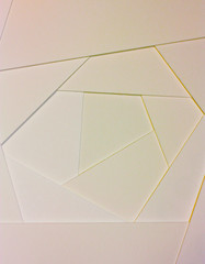 Abstract geometric background in light pastel tones from sheets of thick pale pink, yellow paper, cardboard.