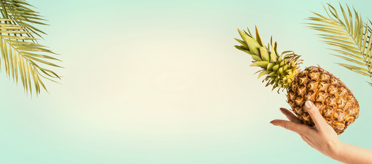 Summer background with palm leaves, female hand with pineapple at sunny sky background, banner or template with copy space for your design