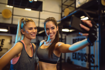 Portrait of young women taking a selfie in the gym.
