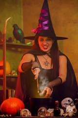 Portrait of witch in black hat with magic wand and cauldron