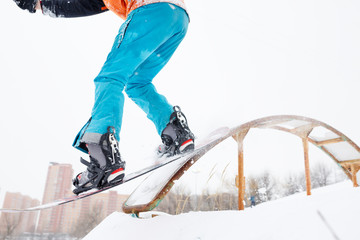 Image from bottom of sportive man skiing on snowboard with springboard