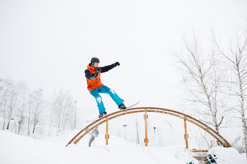 Photo of young sportive man skiing on snowboard with springboard against background of trees