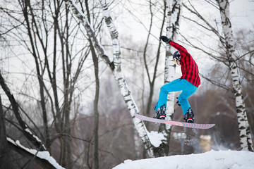 Image of sportsman wearing helmet riding snowboard from snowy slope