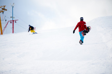 Photo of walking snowboarders in winter park