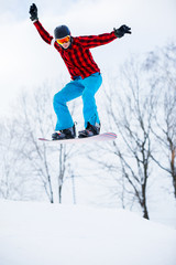 Photo of sportive man with snowboard jumping in snowy resort