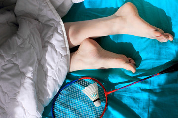 Set Badminton shuttlecock, Racket and woman foot on bed in morning.