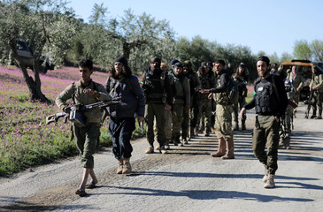 Turkish-backed Free Syrian Army fighters walk together after advancing north of Afrin