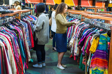 Women browsing through vintage clothing in a Thrift Store.