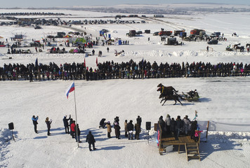 An aerial view shows spectators looking at a Russian Troika during an amateur horse race near Krasnoyarsk
