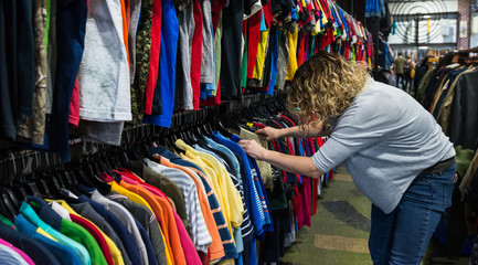 Woman browsing and searching through t-shirts in a thrift store