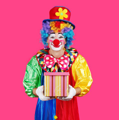 Closeup picture of a clown against pink background presenting a box with a gift