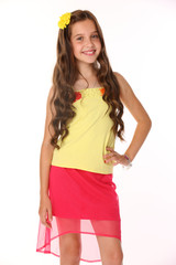 Portrait of a pretty brunette child with chic long hair is stands in a red skirt with bare legs. Beautiful charming happy young teenage girl smiles.