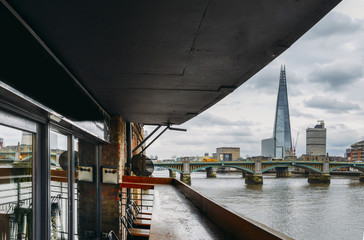 London skyline including the Shard and Southwark Bridge on the River Thames as seen from a comfortable terrace.
