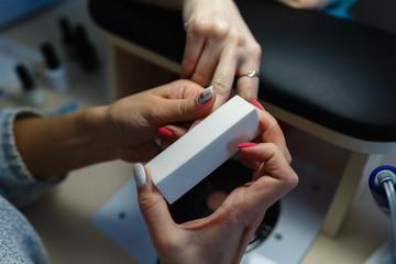 Close-up professional manicure pedicure polishing nail file client.