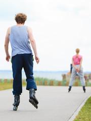 Man rollerblading behind woman on promenade